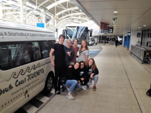 Group of young people posing with the bus at the airport