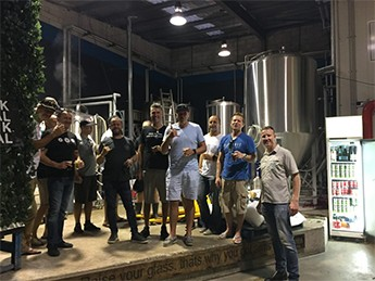 Group of me standing in a brewery wirh beers in their hands