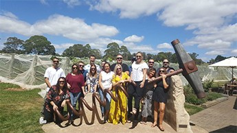 Group of happy people posing with a giant corkscrew sculpture at a winery